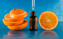 Ätherisches Öl mit orange Scheiben, Flasche und Tropfenzähler stockfotos