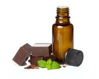 Ätherisches Öl wesentlich und Schokolade mit den tadellosen Blättern lokalisiert lizenzfreies stockfoto