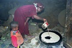 Äthiopische Frau mit Sohn backt injera auf hölzernem Feuer lizenzfreies stockbild