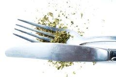 Ätlig marijuana, gaffel och kniv, vit bakgrund Arkivfoton