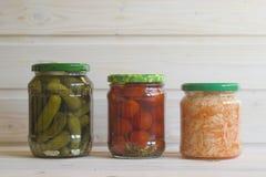 Ättiksgurkor, tomater och surkål i krus på en ljus träbaksida royaltyfria bilder