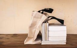 Äußere Stofftasche der Bücher auf hölzerner Tabelle lizenzfreie stockbilder