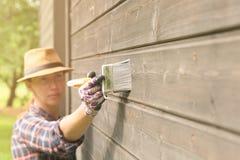 Äußere Wand des Arbeitnehmerin-Malereiholzhauses mit Malerpinsel und hölzerner schützender Farbe stockbilder