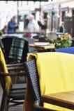 Äußerer Patio eines europäischen Restaurants - Tabellen und schwarz- braune Stühle mit gelben Decken für kühles Wetter lizenzfreie stockfotos