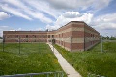 Äußeres des Gefängniszellblockes mit überwuchertem Yard Stockbild