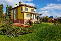 Äußeres des Luxushauses mit grünem Yard, Holzbrücke und Farbe Lizenzfreie Stockfotografie