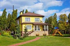 Äußeres des schönen Hauses mit grünem Yard und Kinderplaygro Lizenzfreie Stockfotos