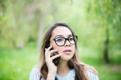 Äußeres Porträt der schönen jungen gelockten Frau, die über Handy im Park spricht Lizenzfreies Stockfoto