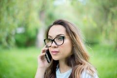 Äußeres Porträt der schönen jungen gelockten Frau, die über Handy im Park spricht Lizenzfreie Stockfotos