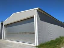 Äußeres von einem Metallhangar für die Herstellung oder Lagerung Seitenansichtgarage mit geschlossenen rollenden Türen mit konkre lizenzfreies stockfoto