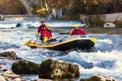 äventyrlig grupp som gör vitt vatten som rafting forsarna av floden Arkivbild