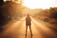Äventyrlig kvinna för ung fotvandring som liftar på vägen Ordna till för affärsföretag av liv Lopplivsstil Låg budget- resande Ad royaltyfria bilder