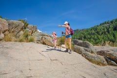 Äventyrliga kvinna och litet barn peka rutten i den Camorza klyftan nära Madrid royaltyfri bild