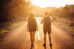 Äventyrliga par för ung fotvandring som liftar på vägen Affärsföretag av liv Lopplivsstil Låg budget- resande äventyrade arkivbild