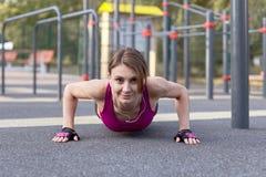 健身活动的华美的亭亭玉立的年轻女人在室外sportsground,推挤上升和下来 与看起来的正面图对凸轮 免版税图库摄影