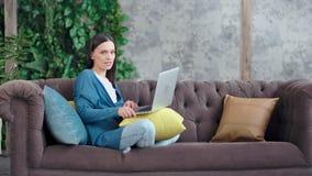 偶然微笑的女实业家在家与盘的腿坐享受周末的长沙发 股票视频