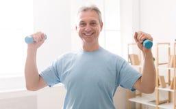 做与哑铃的成熟人健身训练 免版税图库摄影