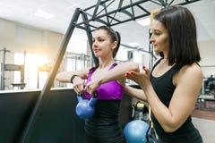 做与重量的个人健身教练员教练和帮助的客户妇女锻炼在健身房 健身,体育,训练,人们, 免版税库存照片