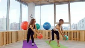 做健身的年轻女人在拿着球的演播室 做准备 股票录像