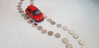 做它的方式的红色菲亚特500 abarth玩具在路线由一以色列锡克尔硬币做成 库存图片