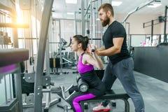 做在健身房的个人健身教练员教练和帮助的客户妇女锻炼 体育,配合,训练,人概念 免版税库存图片