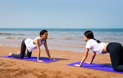 做在海滩的女孩俯卧撑 免版税库存图片