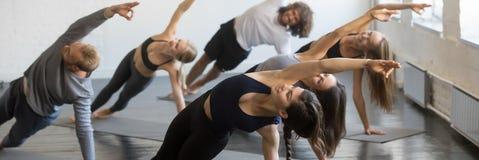 做旁边板条姿势瑜伽Vasisthasana锻炼的女孩和人 免版税库存图片