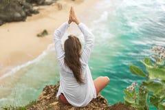 做瑜伽的女孩在日落海景巴厘岛 免版税库存照片