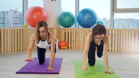 做瑜伽的年轻女人在瑜伽席子的演播室 腿的锻炼 拿着平衡 股票视频