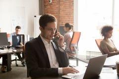 做电话谈判的咨询的顾客的严肃的商人看膝上型计算机 库存图片