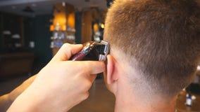 做男性理发的美发师的胳膊对有飞剪机的顾客在时髦沙龙 剪头发的发式专家的手 股票视频