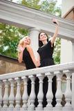 做selfie的一件黑礼服的两个年轻俏丽的女孩 免版税库存图片