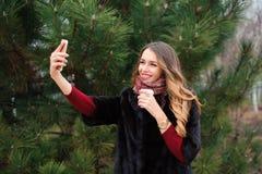 做selfie的女孩在秋天公园,走在公园的可爱的妇女 图库摄影