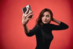 做selfie照片的一个时髦的年轻深色的女孩的画象射击与葡萄酒影片照片照相机在珊瑚红色 库存照片