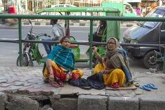 印度妇女缝合衣裳坐边路反对城市交通背景  免版税图库摄影