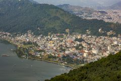博克拉的看法在湖Phewa附近的有在水的小船的,以绿色山城市为背景 库存图片