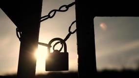 反对天空和太阳在日落在老和生锈的挂锁的链子垂悬 股票录像