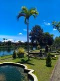 反对天空蔚蓝和湖的美丽的庭院 免版税库存图片