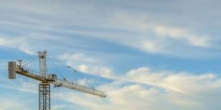 反对天空蔚蓝的塔吊与松的云彩 免版税库存照片