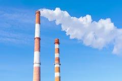 反对多云天空的发怒的管子能源厂 库存照片