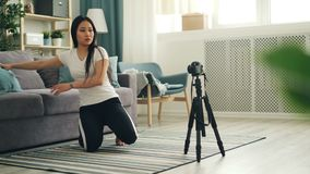 可爱的亚裔博客作者在三脚架安装照相机并且调整设备然后坐地板和记录 股票录像