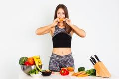 可爱的健身妇女,训练了女性吃桔子,有机食品的适合力量运动确信的年轻女人爱好健美者 库存图片