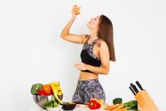 可爱的健身妇女,训练了女性吃桔子,有机食品的适合力量运动确信的年轻女人爱好健美者 免版税库存图片