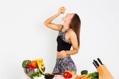 可爱的健身妇女,训练了女性吃桔子,有机食品的适合力量运动确信的年轻女人爱好健美者 免版税库存照片