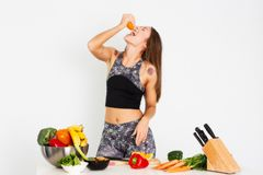 可爱的健身妇女,训练了女性吃桔子,有机食品的适合力量运动确信的年轻女人爱好健美者 库存照片