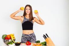 可爱的健身妇女,训练了女性适合力量运动确信的年轻女人爱好健美者cuting的桔子,有机食品 免版税图库摄影
