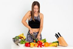 可爱的健身妇女,训练了女性适合力量运动确信的年轻女人爱好健美者cuting的桔子,有机食品 库存照片