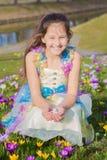 可爱的女孩收集复活节在花中的朱古力蛋 免版税库存图片