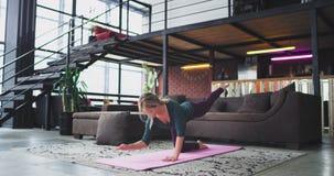 可爱的运动的女子实践的瑜伽在家做在席子的早晨猎鸟犬锻炼在现代的客厅 影视素材