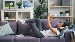 可爱的非裔美国人的女孩听到在说谎在居住的沙发的耳机的音乐和移动的手和腿 股票视频